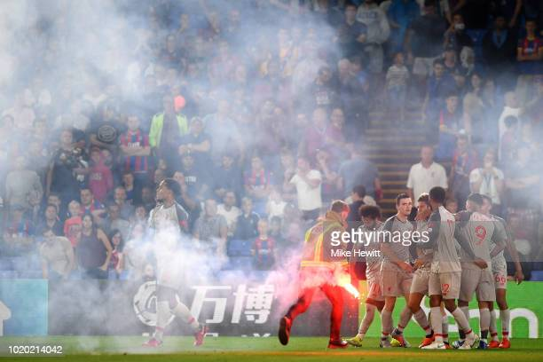 A flare is removed from the pitch following Sadio Mane of Liverpool celebrating scoring his team's second goal with team mates during the Premier...