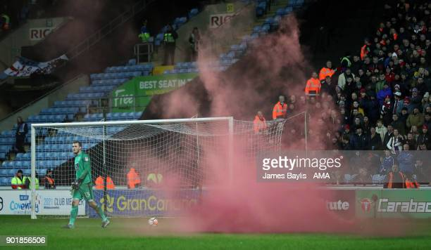 A flare lands near Liam O'Brien of Coventry City during The Emirates FA Cup Third match between Coventry City and Stoke City at Ricoh Arena on...