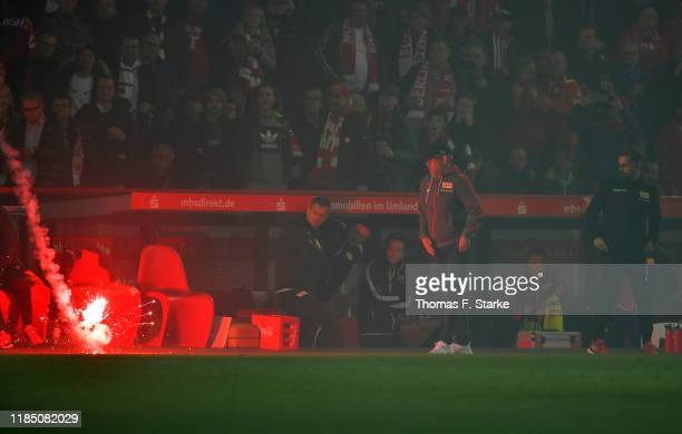 A flare lands next to Urs Fischer Head Coach of 1 FC Union Berlin during the Bundesliga match between 1 FC Union Berlin and Hertha BSC at Stadion An...