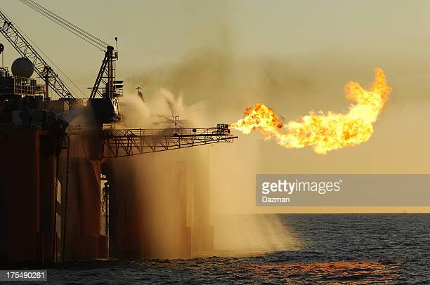 flare on an ocean oil rig. - flare stack stock photos and pictures