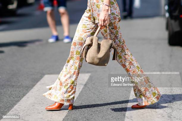 Flared pants with floral prints and a bag outside Acne Studios during Paris Fashion Week Womenswear Fall Winter 2019 on July 1 2018 in Paris France