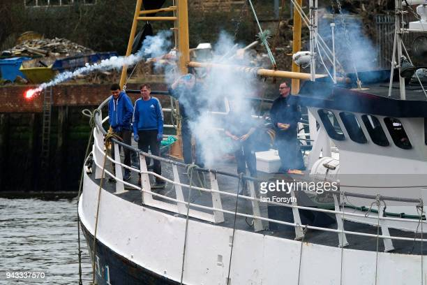 Flares are fired from the deck of a fishing boat as a flotilla of boats head downriver on the River Tyne after fishermen take part in a nationwide...
