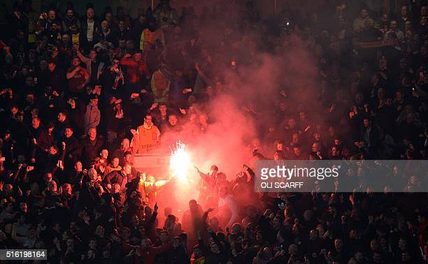 Flares are lit by the Liverpool supporters during the UEFA Europa League round of 16 second leg football match between Manchester United and...