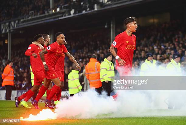 Flares are removed from the pitch as Sadio Mane of Liverpool scores their first goal during the Premier League match between Everton and Liverpool at...