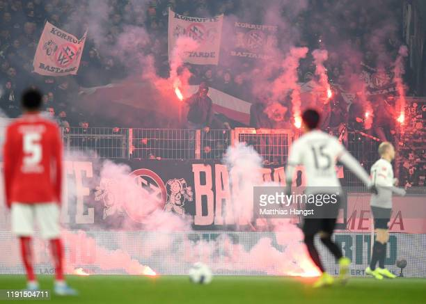 Flares are seen on the pitch as players wait to kick-off prior to the Bundesliga match between 1. FSV Mainz 05 and Eintracht Frankfurt at Opel Arena...