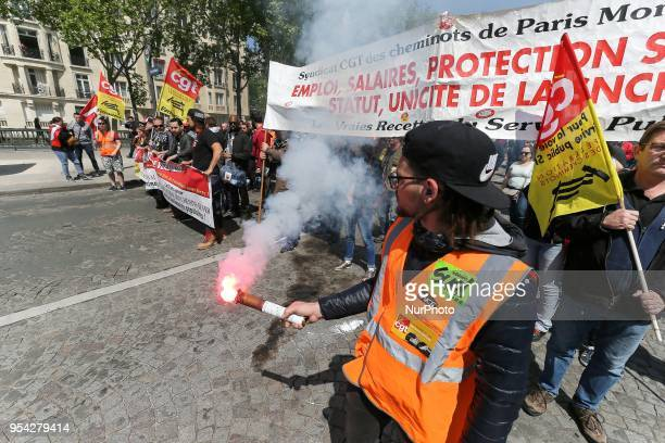 Flares emit smoke as railway workers and supporters take part in a gathering of employees of the stateowned rail operator SNCF called by CGT Unsa SUD...