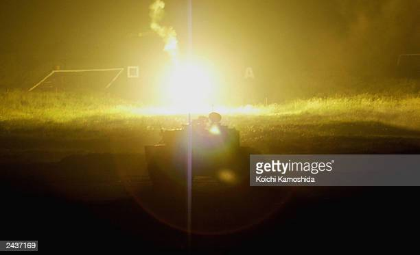 Flares light the area as Japanese Military selfdefence forces conduct a nighttime tank drill on August 28 2003 in Gotenba Shizuoka Prefecture Japan...