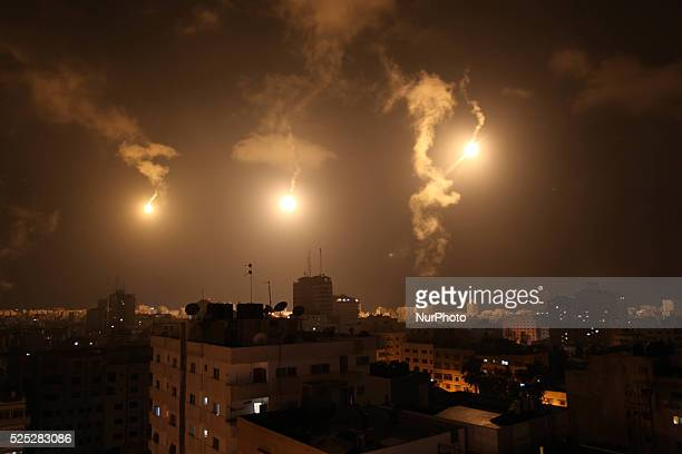 flares light the sky over Gaza as a trace of Israeli shelling bottom right is seen from Gaza City in the northern Gaza Strip Monday July 28 2014 A...