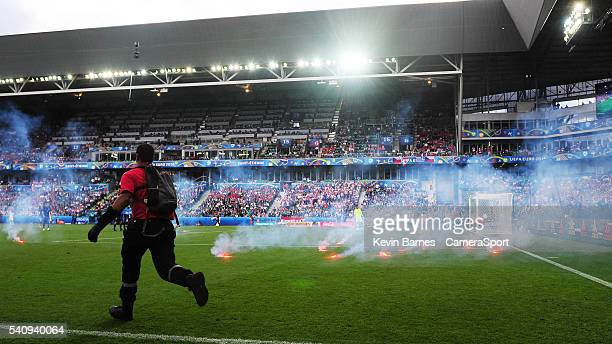 Flares litter the pitch as fire marshalls rush in to remove them during the UEFA Euro 2016 Group D match between Czech Republic and Croatia at Stade...