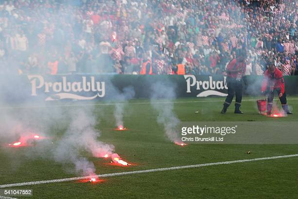 Flares thrown by Croatian fans litter the pitch during the UEFA Euro 2016 Group D match between the Czech Republic and Croatia at Stade...
