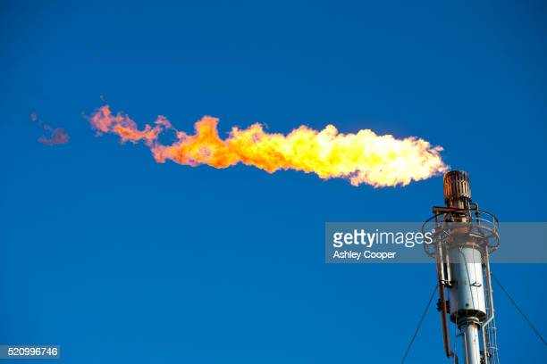flaring off gas at the flotta oil terminal on the island of flotta in the orkney's scotland, uk. - hydrocarbon stock pictures, royalty-free photos & images