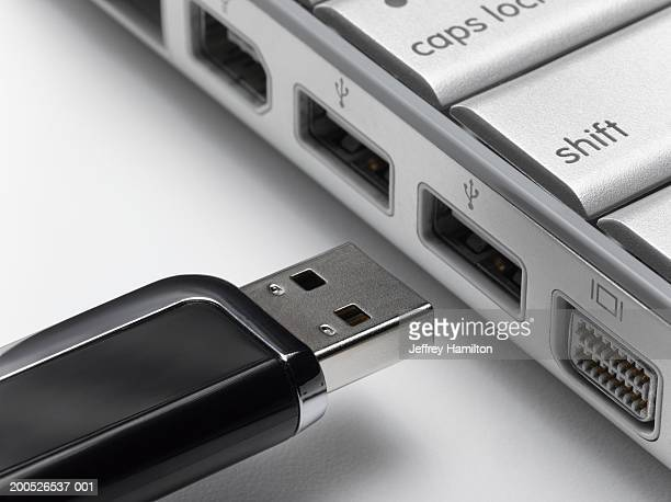 USB flash drive about to connect to laptop, close-up