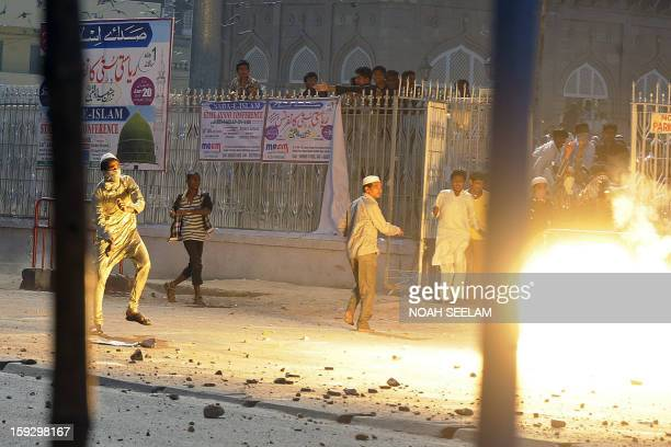 A flash from a tear gas shell is seen as supporters of the MajliseIttehadul Muslimeen clash with police outside the historic Mecca Masjid following...
