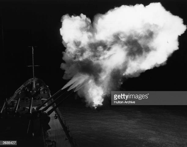 A flash from a triple salvo lights up the night as guns on the USS Canberra fire at military targets on the North Vietnamese coast