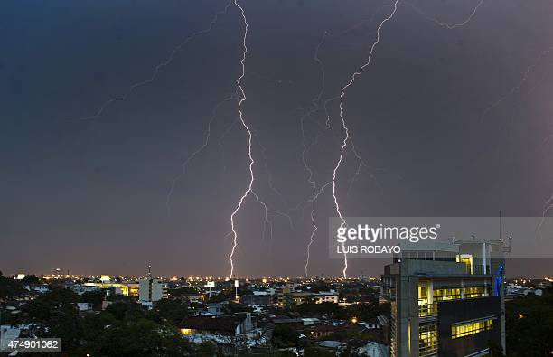 A flash of lightning during a thunderstorm at night over the city of Cali Valle del Cauca department Colombia on May 27 2015 AFP PHOTO / LUIS ROBAYO