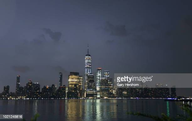 A flash of lightning illuminates the sky over lower Manhattan and One World Trade Center in New York City on August 17 2018 as seen from Jersey City...