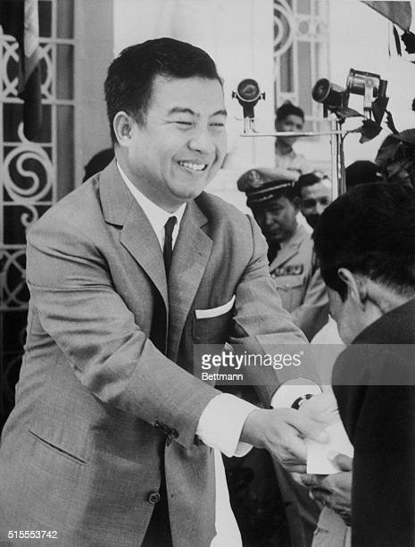 Flashing a bright smile Cambodia's Prince Norodom Sihanouk wears a conservative western business suit as he presents a gift to one of his subjects at...