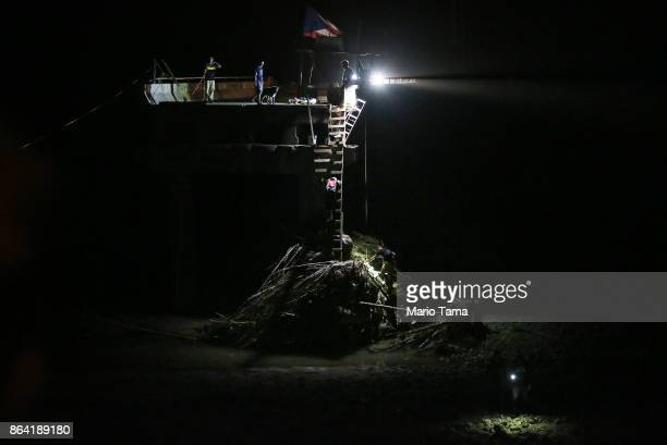 Flashlights and car headlights are used to help people descend makeshift ladders reaching to the bottom of a broken bridge spanning the Vivi River on...