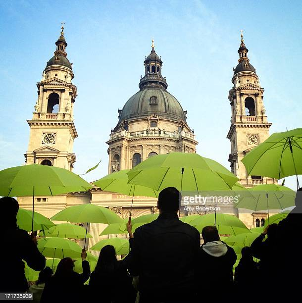 Flashmob dances with green umbrellas in front of St. Stephen's Cathedral in Budapest, Hungary on November 17, 2012.