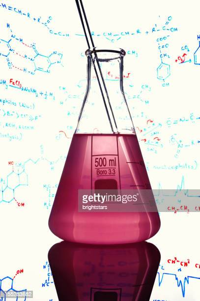 flask surrounded by chemical formulas - potion stock photos and pictures