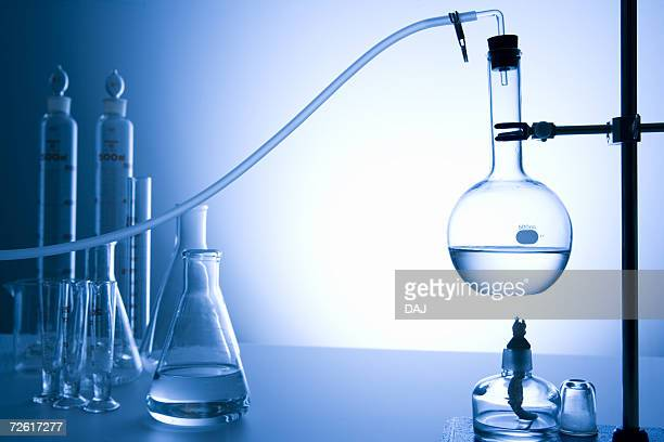 Flask with liquid set over burner, front view, toned image, blue background, differential focus