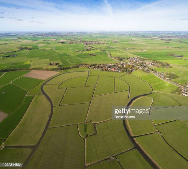 flat and cultivated landscape with river bend in foreground - groningen provincie stockfoto's en -beelden