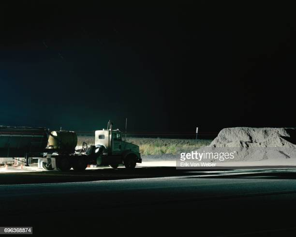 flat bed truck on side of road at construction site