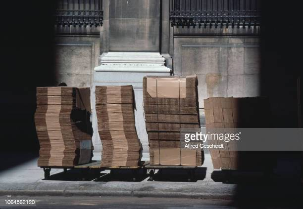 Flat corrugated boxes piled up on trolleys outside a building in Manhattan New York City US 1991
