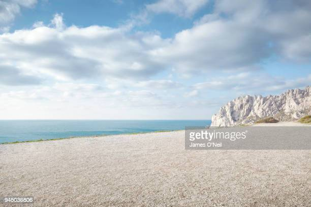 flat gravel plateau next to ocean with background rocks - gravel stock pictures, royalty-free photos & images