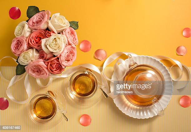 Flat lay afternoon tea set on yellow background.