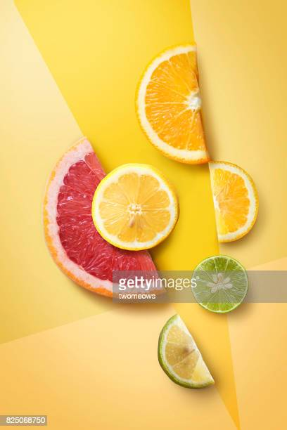 Flat lay assorted citrus fruits slice on graphical design background.