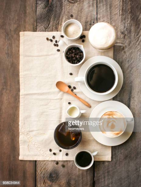 Flat lay assorted coffee drink related ingredients on wooden table top.