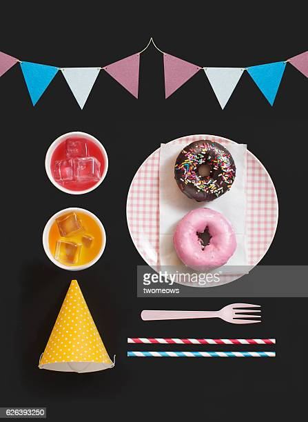 Flat lay assortment arrangement party food and drinks, hat and decoration flag on black background.