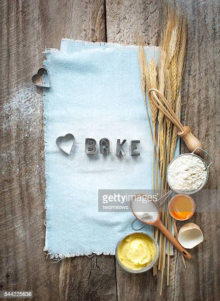 Flat lay baking utensils and ingredient on rustic wooden background.