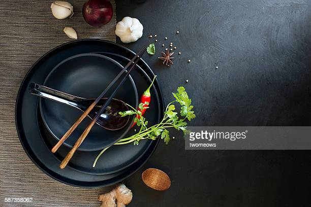 Flat lay Chinese cuisine recipe ingredient herb and spices and tableware on black texture background.