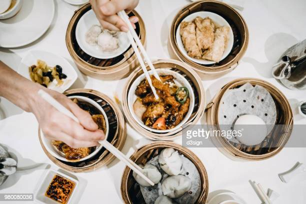 Flat lay Chinese dim sum time, various traditional dim sum freshly served on table and human hands picking up with chopsticks