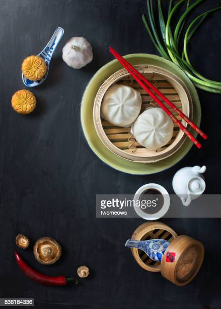 Flat lay Chinese food and drink on moody rustic table top.