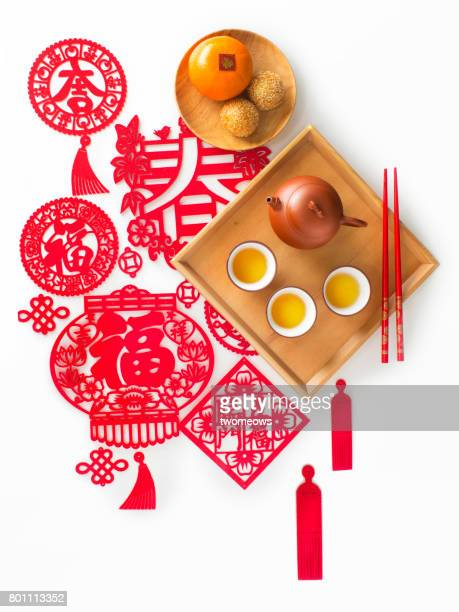 Flat lay Chinese New Year snack and hot tea on traditional paper cutting background.