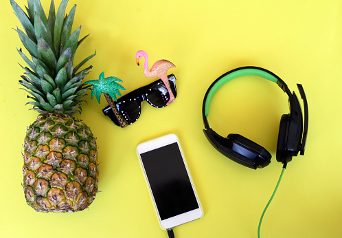 Flat lay composition with pineapple, smartphone, sunglasses and headphones on yellow background - gettyimageskorea