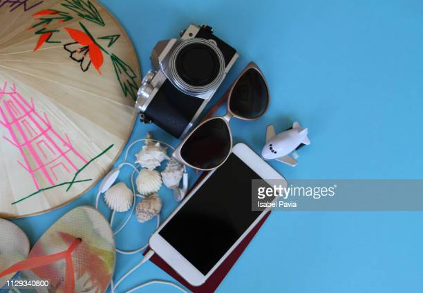 Flat lay composition with summer accessories, camera, passport, mobile phone and space for text on blue background. Travel blogger