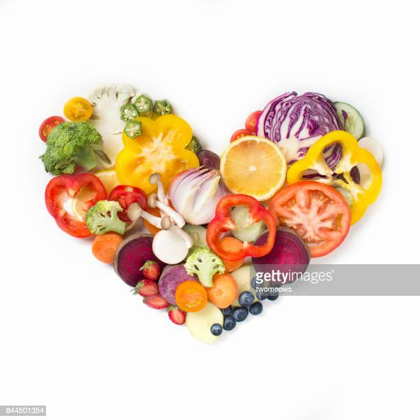 Flat lay conceptual vegan food in heart shape on white background.