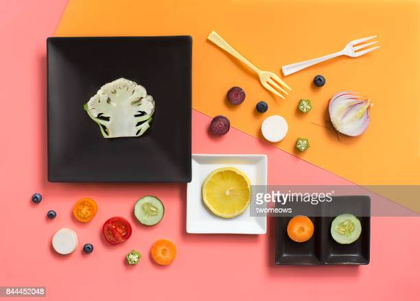 Flat lay conceptual vegan food still life on coloured background.