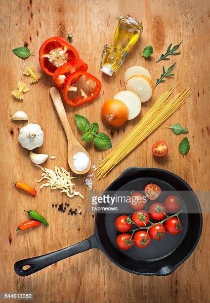 Flat lay cooking pan with freshly cut paste recipe ingredient on rustic wooden table top.