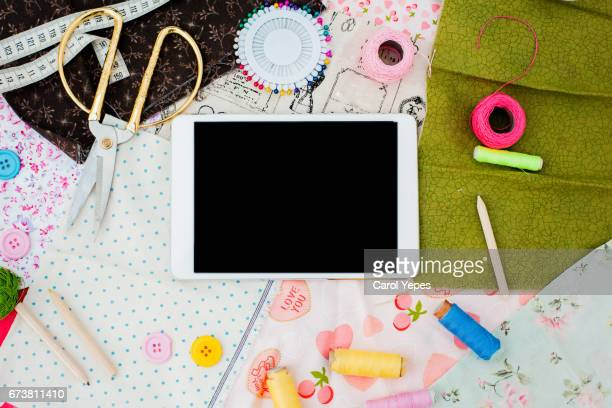 flat lay  digital tablet and sewing items.White background
