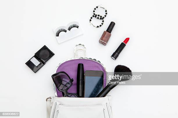 flat lay feminine arrangement with mobile phone, accessories, purse, cosmetics on white, flat lay, top view