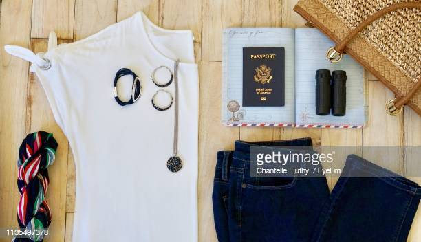 flat lay image of clothes with traveling equipment on wooden table - womenswear stock pictures, royalty-free photos & images