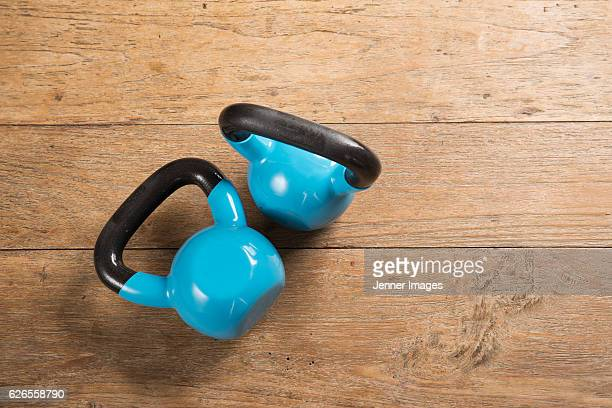 Flat Lay image of kettlebells on a wooden floor.