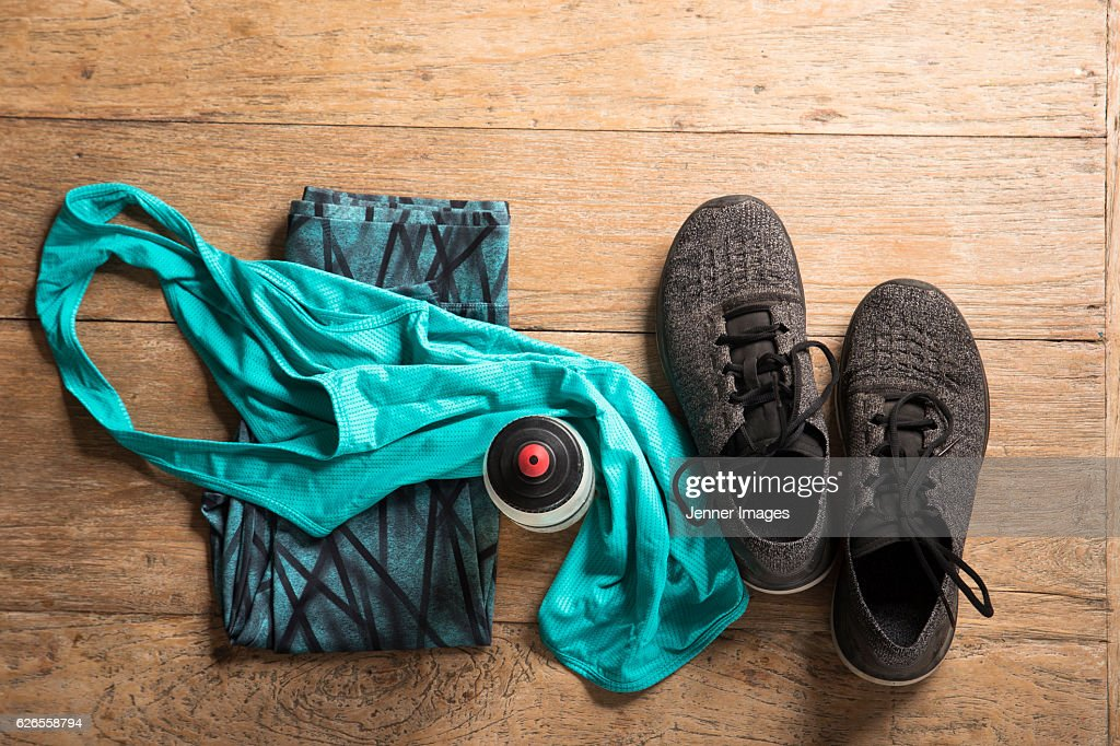 Flat Lay image of sports clothes and shoes on a wooden floor. : Stock Photo