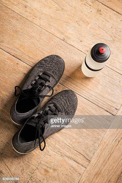 Flat Lay image of sports shoes on a wooden floor.