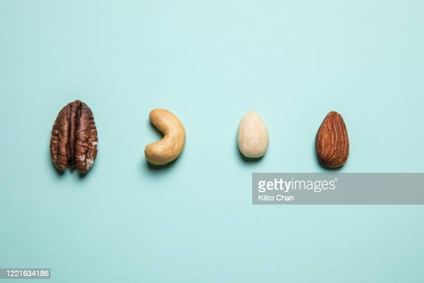 flat lay mixed nuts against blue background - cashew stock pictures, royalty-free photos & images